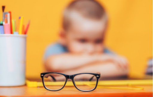 A pair of glasses on a school desk with a blurred boy sitting in the background, highlighting his vision problem's